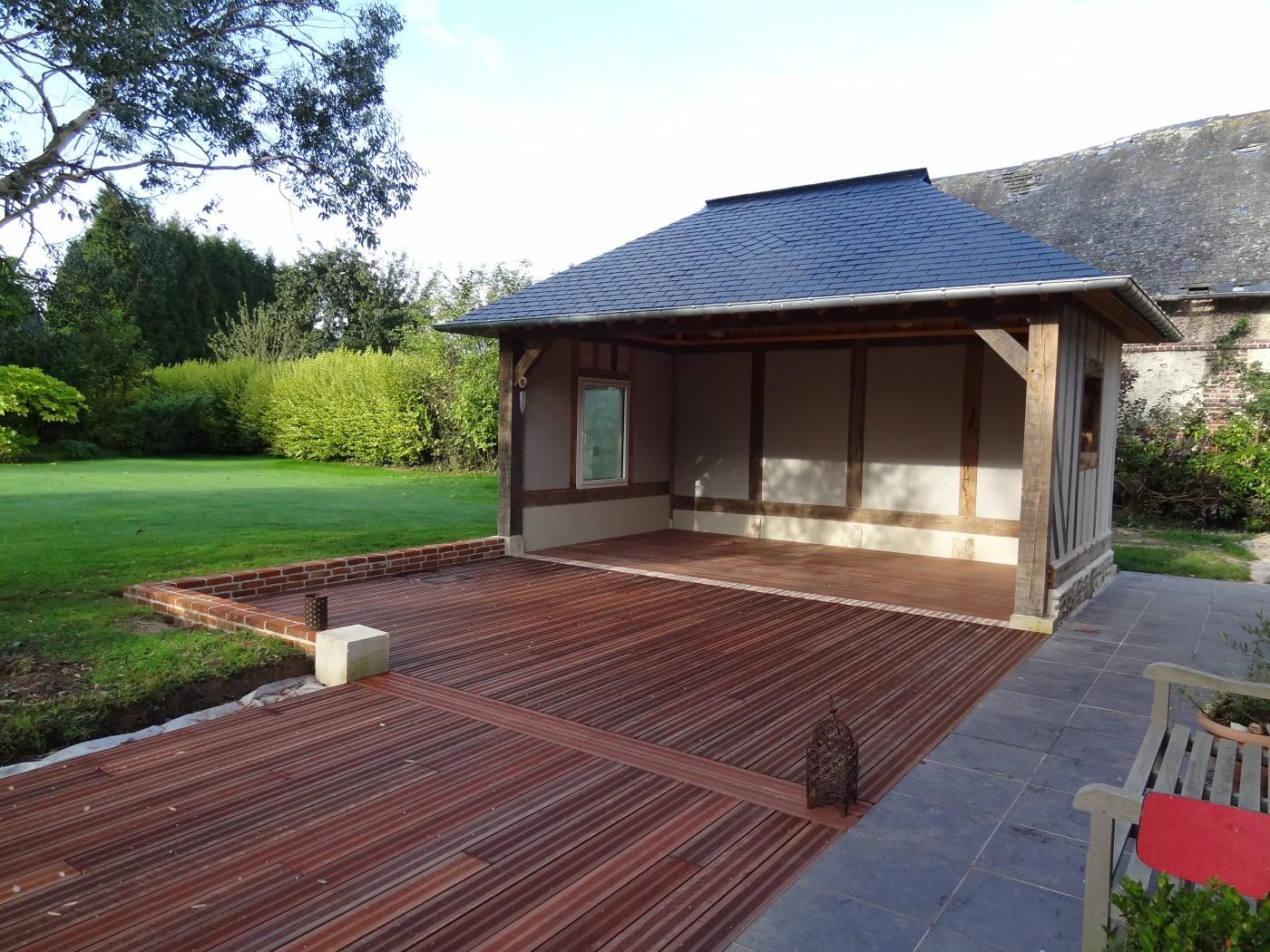 Devant le petit bâtiment normand à colombages qui accueillera la table de ping pong, une terrasse en bois exotique